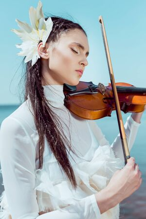 Portrait of beautiful woman in white swan costume with violin closing eyes, playing music on sky background