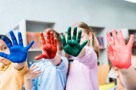 Selective focus of multicultural kids covering faces with colorful hands
