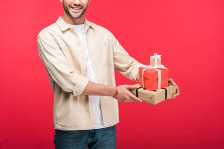 Cropped view of smiling man holding presents On pink background