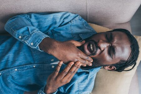 Top view of African American man lying on sofa and suffering from jaw pain Stockfoto