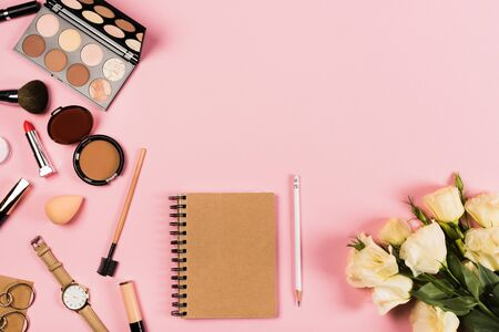 Top view of wristwatch, earrings, flowers, notebook, pencil and decorative cosmetics on pink background