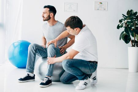 Physiotherapist massaging leg of patient sitting on fitness ball in hospital