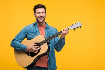 Handsome smiling man playing acoustic guitar isolated on yellow background