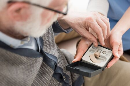 High angle view of elderly man looking at box with hearing aid Stock Photo