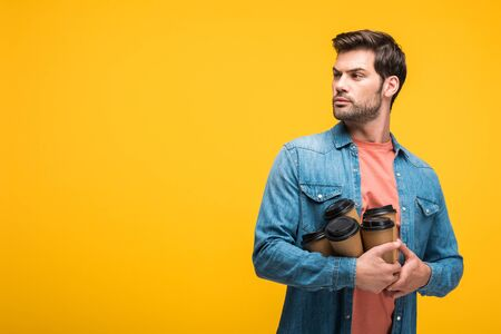 Confused handsome man with coffee to go isolated on yellow background with copy space