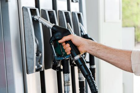 Cropped view of man holding fuel nozzle at gas station Stock Photo