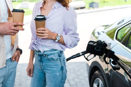 Cropped view of man standing with hand in pocket near woman holding paper cup at gas station Stockfoto