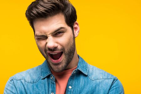 Excited handsome man winking and looking at camera isolated on yellow background 版權商用圖片