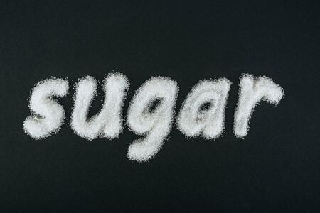 Top view of word sugar made of white sugar crystals on black background Imagens