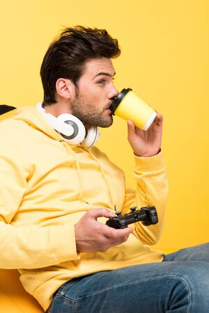 Man drinking coffee to go and playing Video Game isolated on yellow background
