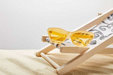 Yellow sunglasses and deck chair on sand on grey background