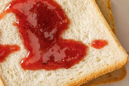 Close up view of toasts with jam on white plate