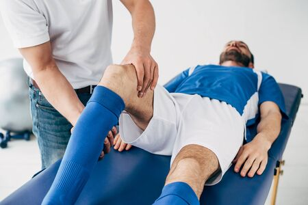 Physiotherapist massaging leg of football player in hospital Stockfoto