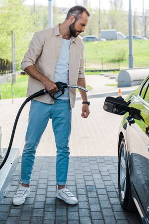 Handsome man holding fuel nozzle near black car at gas station
