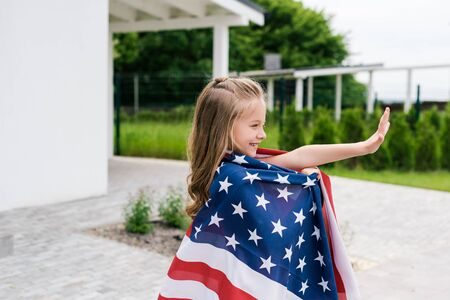 Happy kid waving hand while standing with American flag near house