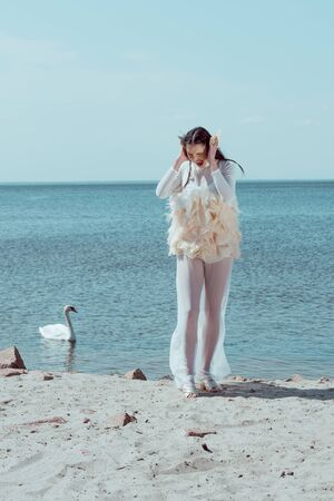 Adult woman in white swan costume yelling, sanding on sandy beach, near birds