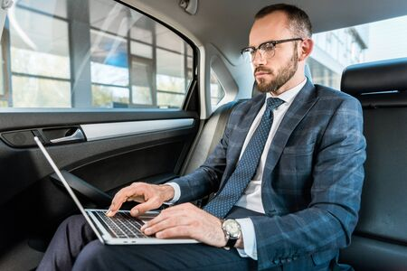Low angle view of handsome businessman in glasses typing on laptop in car