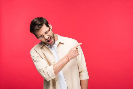 Happy handsome man pointing with finger at copy space isolated on pink background Stock Photo