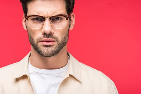 Dissatisfied handsome man in glasses isolated on pink background Stockfoto