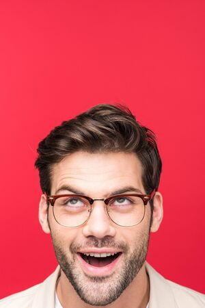Surprised handsome man in glasses looking up isolated on pink background