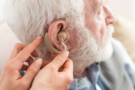 Cropped view of woman helping grey haired man, wearing hearing aid Stock Photo