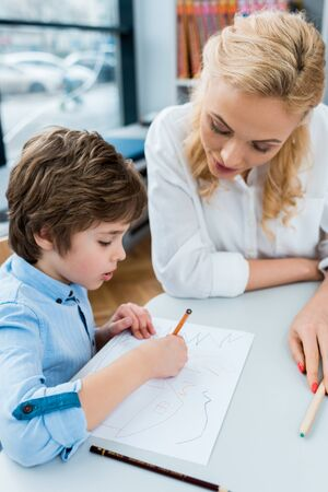 Selective focus of woman looking at cute child drawing on paper Stock Photo