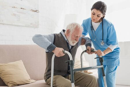 Doctor helping to retired man, getting up from sofa Banco de Imagens