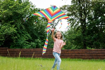 Happy child running with colorful kite on green grass outside 版權商用圖片