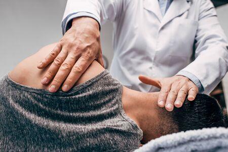 Chiropractor in white coat massaging neck of man
