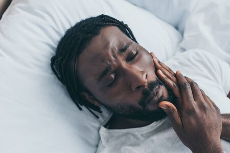 Unhappy African American man suffering from jaw pain while lying in bed