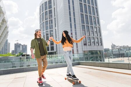 Cheerful woman holding hands with man, riding on skateboard on roof