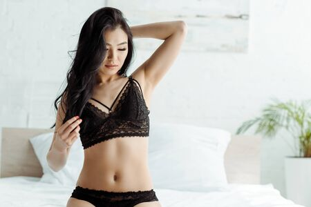 Pretty brunette Asian woman in lace black underwear in bedroom