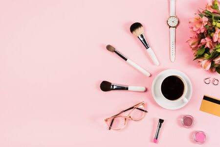 Flat lay with cup of coffee, flowers, decorative cosmetics, credit card and accessories on pink background