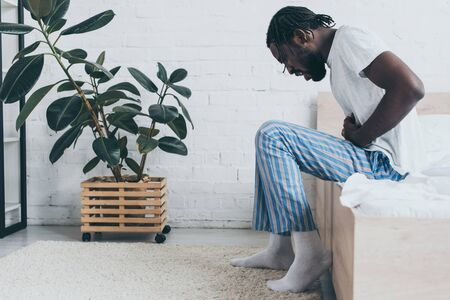 Young African American man suffering from stomach ache while sitting on bed Reklamní fotografie