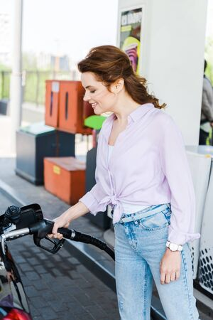 Happy woman holding fuel pump while refueling automobile with benzine at gas station