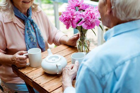 老夫妇捧着杯子坐在茶壶旁的剪影
