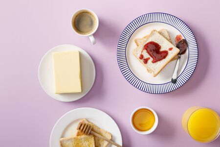 Top view of butter, coffee, orange juice, toasts with honey and jam on plates on violet background Stock fotó