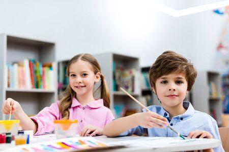 Enfoque selectivo de niños alegres mirando a cámara y sosteniendo pinceles