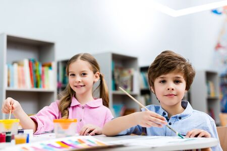 Selectieve focus van vrolijke kinderen die naar de camera kijken en penselen vasthouden