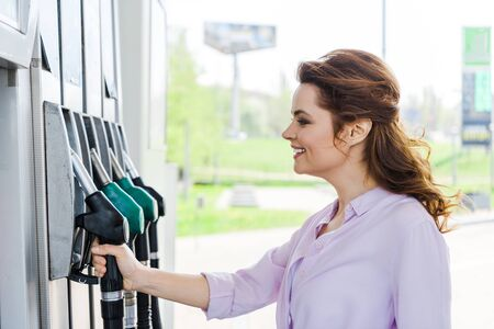 Happy woman holding fuel pump while smiling at gas station