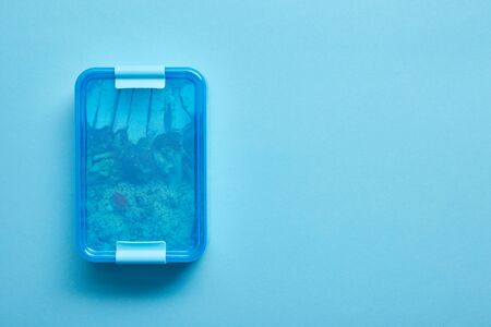 Top view of lunch box with delicious healthy meal on blue background