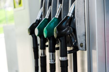 Selective focus of green and black fuel pumps at gas station