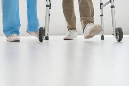 Cropped view of doctor and senior man walking on floor with copy space 写真素材