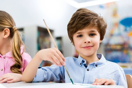 Happy kid holding paintbrush near child and looking at camera