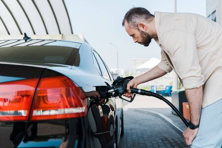 Bearded man holding fuel pump and refueling black car at gas station Zdjęcie Seryjne