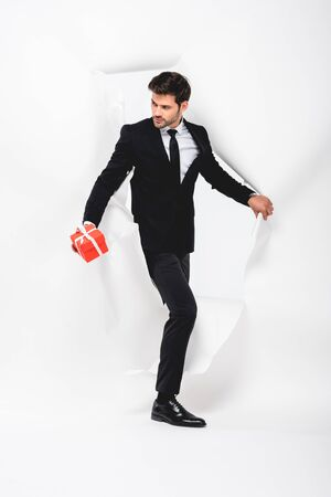 Handsome man in suit with present walking through hole in paper on white background Stock Photo