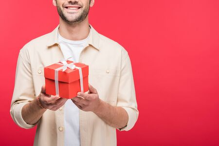 Cropped view of smiling man holding present isolated on pink background with copy space
