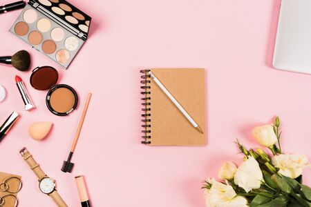 Top view of wristwatch, earrings, flowers, notebook with pencil and decorative cosmetics on pink background