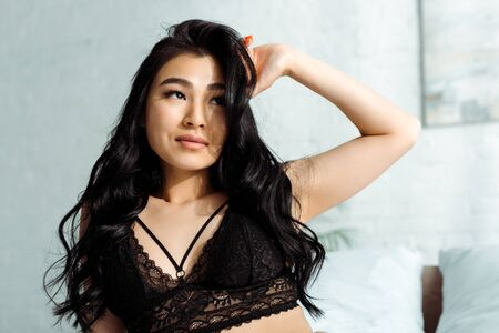 Sensual Asian woman in sexy lace bra touching hair in bedroom Stock Photo