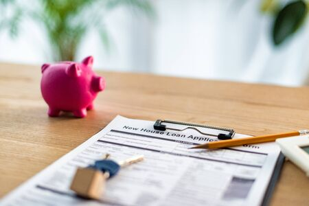 Selective focus of clipboard with new house loan lettering on document near keys, pencil  and pink piggy bank